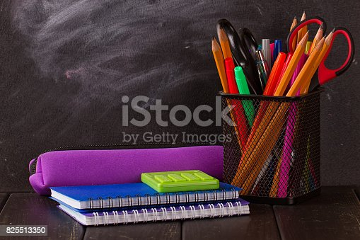 istock Multicolor pencils with black chalkboard 825513350