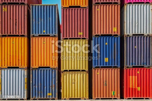 Multicolor shipping containers stacked high at a port.
