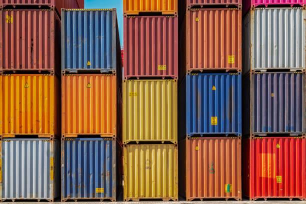 Mehrfarbige Versandcontainer hoch an einem Hafen gestapelt. – Foto