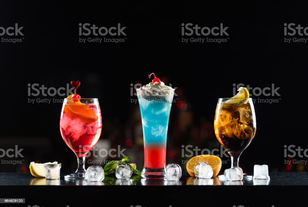Multi-colored alcoholic cocktails with citrus and berries in glasses of different shapes on the bar. royalty-free stock photo