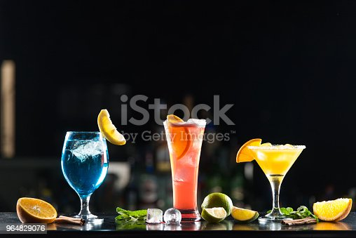 istock Multi-colored alcoholic cocktails with citrus in glasses of different shapes on the bar. 964829076