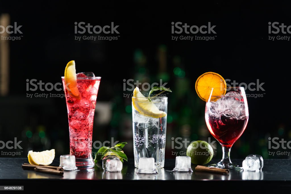 Multi-colored alcoholic cocktails with citrus in glasses of different shapes on the bar. royalty-free stock photo
