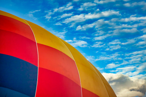 yellow red blue balloon against the blue sky with clouds