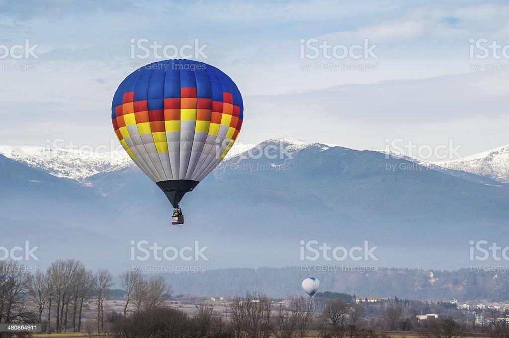 Multicolored Balloon in the blue sky Multicolored Balloon in the blue cloudy sky. Mountain background Adventure Stock Photo