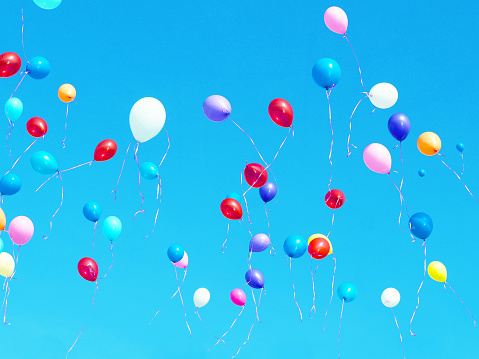 Multicolored balloons filled with helium in the light blue cloudless sky. Flying multicolor balls. Holiday concept