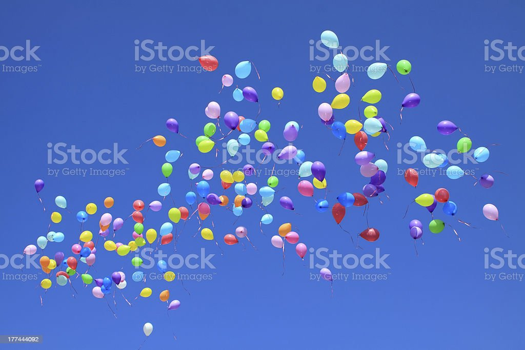 Multicolored balloons released into a clear blue sky stock photo