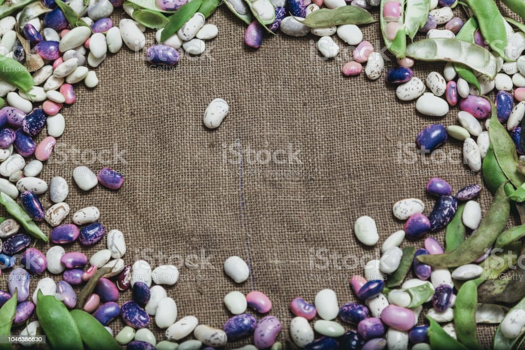 Multicolored beans lie on burlap stock photo