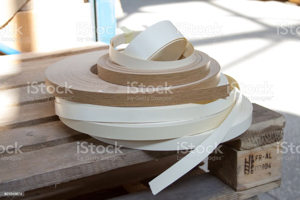 Multicolored bobbins of PVC edge and melanin for the manufacture of furniture. Lie pyramid. stock photo
