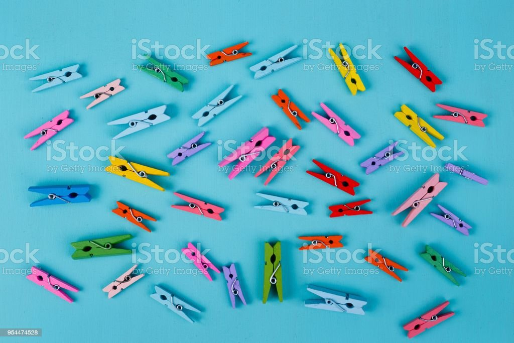 Multicolored bright clothespins on blue background stock photo