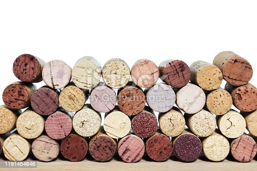 Multicolored bright corks from wine bottles on a wooden table isolated on a white background. Rows of corks with stain of red wine.