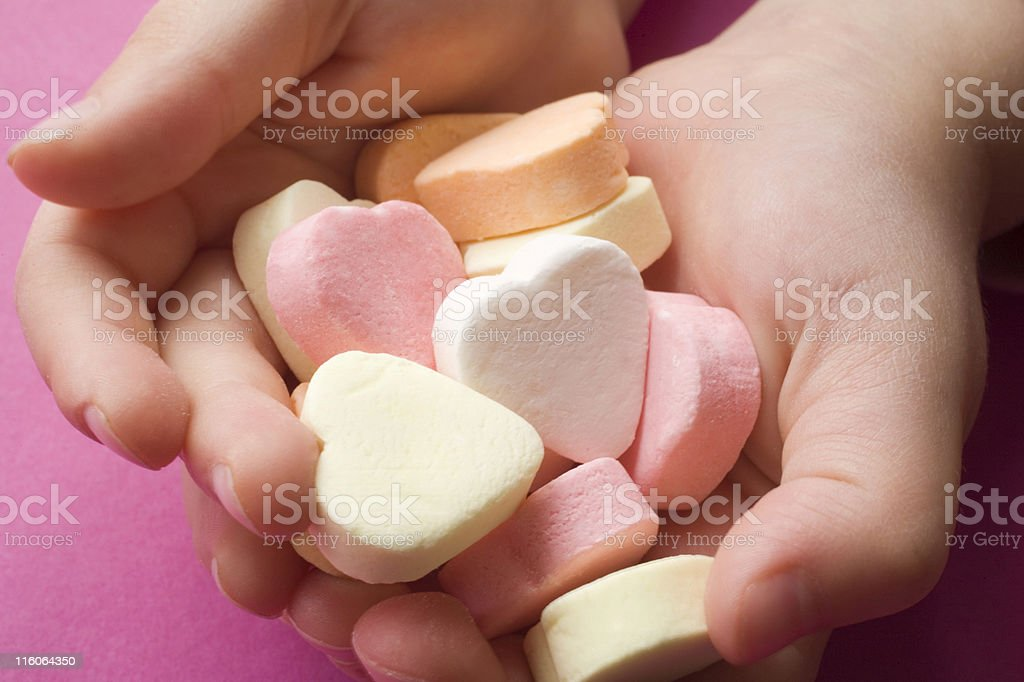 multicolored candy hearts in the hands of a child royalty-free stock photo
