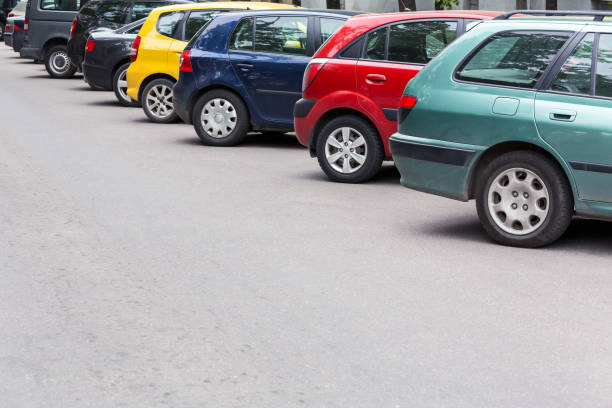 multicolored cars parked diagonally at parking lot in the street - inmóvil fotografías e imágenes de stock