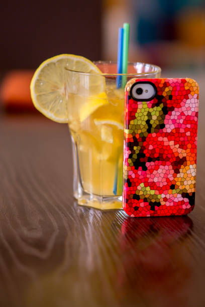 A multi-colored cell-phone cover and a juice coctail in a glass stock photo