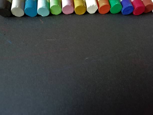 Multi-colored chalk on a black background with a place for text stock photo