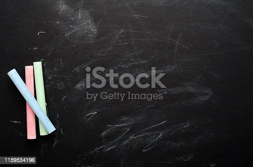 istock Multi-colored chalk on a painted black board. School board, conceptual background. Copy space, top view, flat lay. 1159534196