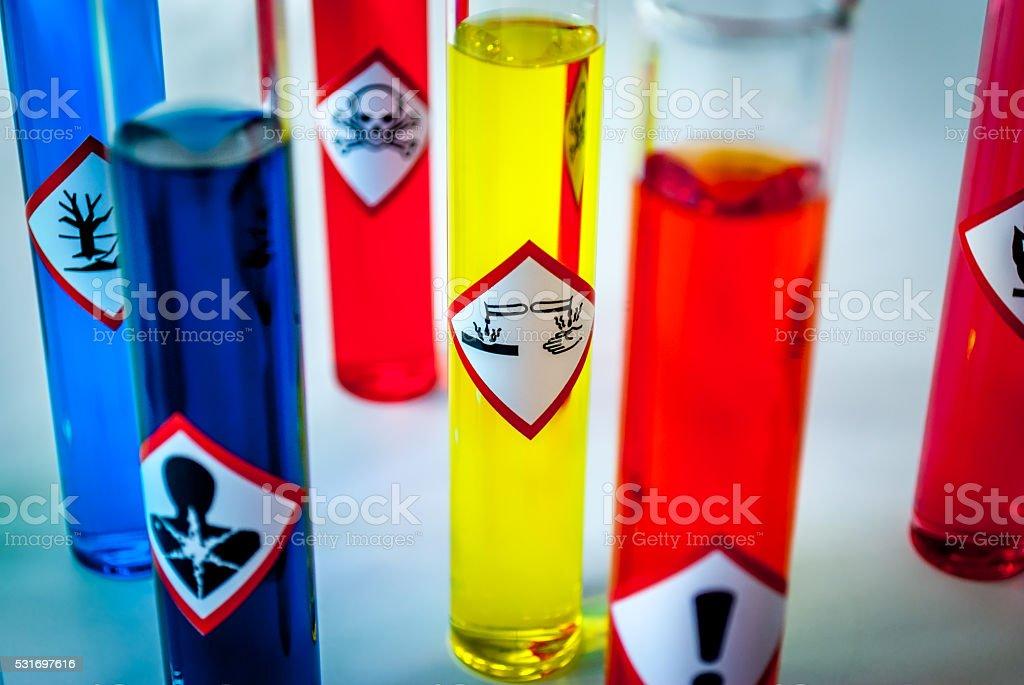 Multicolored Chemistry vials - Focus on corrosive danger stock photo