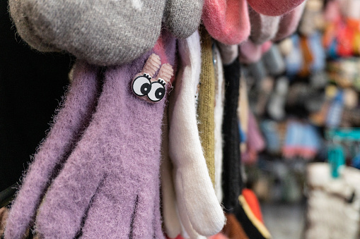 Multicolored children's winter gloves at the market rows. High quality photo