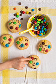 Multi-colored chocolate candy dragees and Chocolate Chips Homemade Cookies and sweets in a yellow ceramic bowl on a white napkin, Child hand takes cookie
