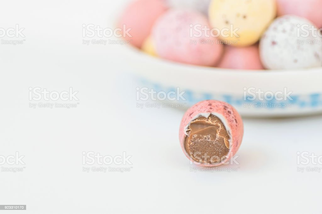 Multicolored Chocolate Candy Speckled Easter Eggs on Plate on Tabletop. One Bitten Off. Holiday Poster Banner Template with Copy Space for Text. stock photo
