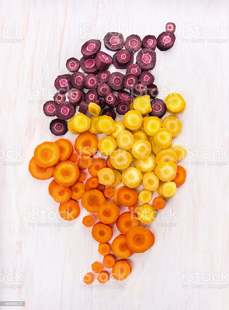 multicolored chopped carrots on white wooden table stock photo