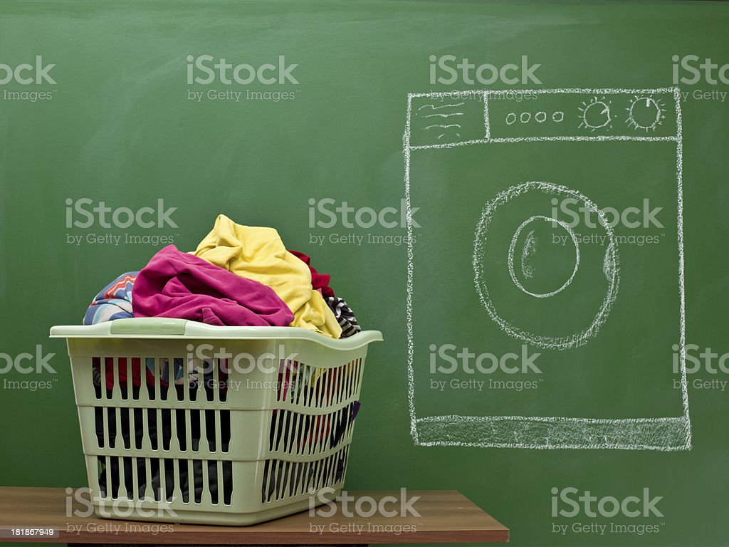 Multicolored clothes in laundry basket and washer machine on blackboard royalty-free stock photo