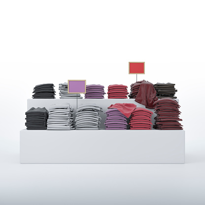 Multi-colored clothes on shelves with price tags in front of white background and copy space. 3D rendered image.