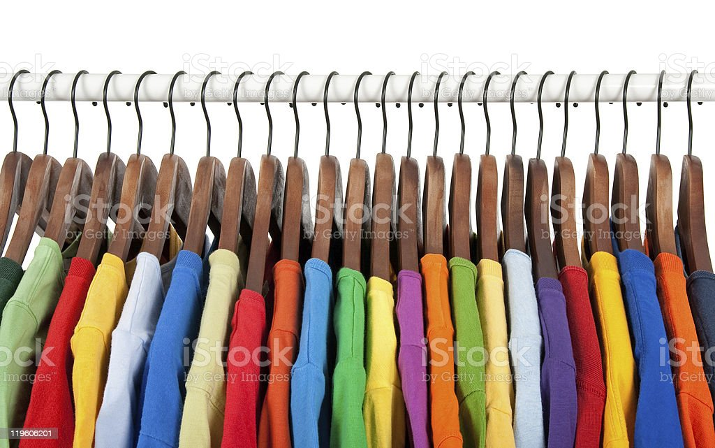 Multicolored clothes on wooden hangers stock photo