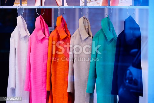 side view of multicolored coats inside store.