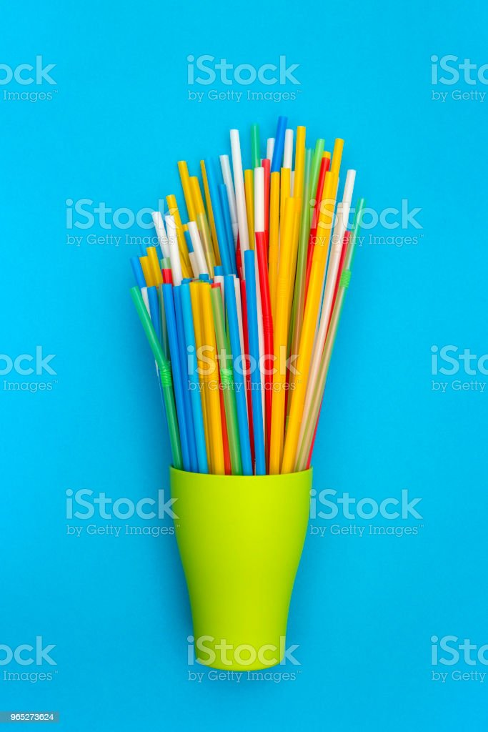 Multi-colored cocktail tubes in a green cup on a blue background zbiór zdjęć royalty-free