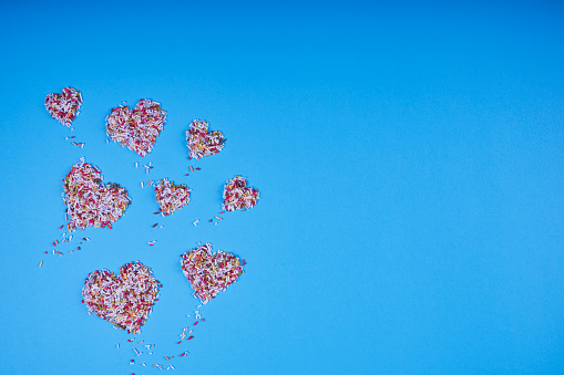 Multicolored confectionery noodle hearts on blue background.