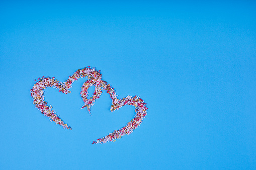 Multicolored confectionery noodle hearts on blue background. St. Valentine's Day