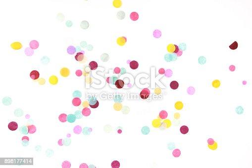 Multicolored confetti on white background. Festive backdrop for your design.