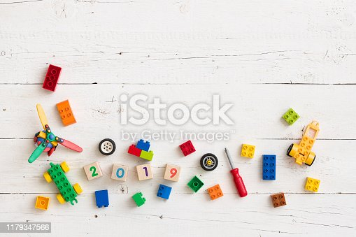 istock Multi-colored cubes of wood and plastic on a wooden background. Wooden cubes with the numbers of the year 2019. Toys and other equipment for the early development of the child. 1179347566