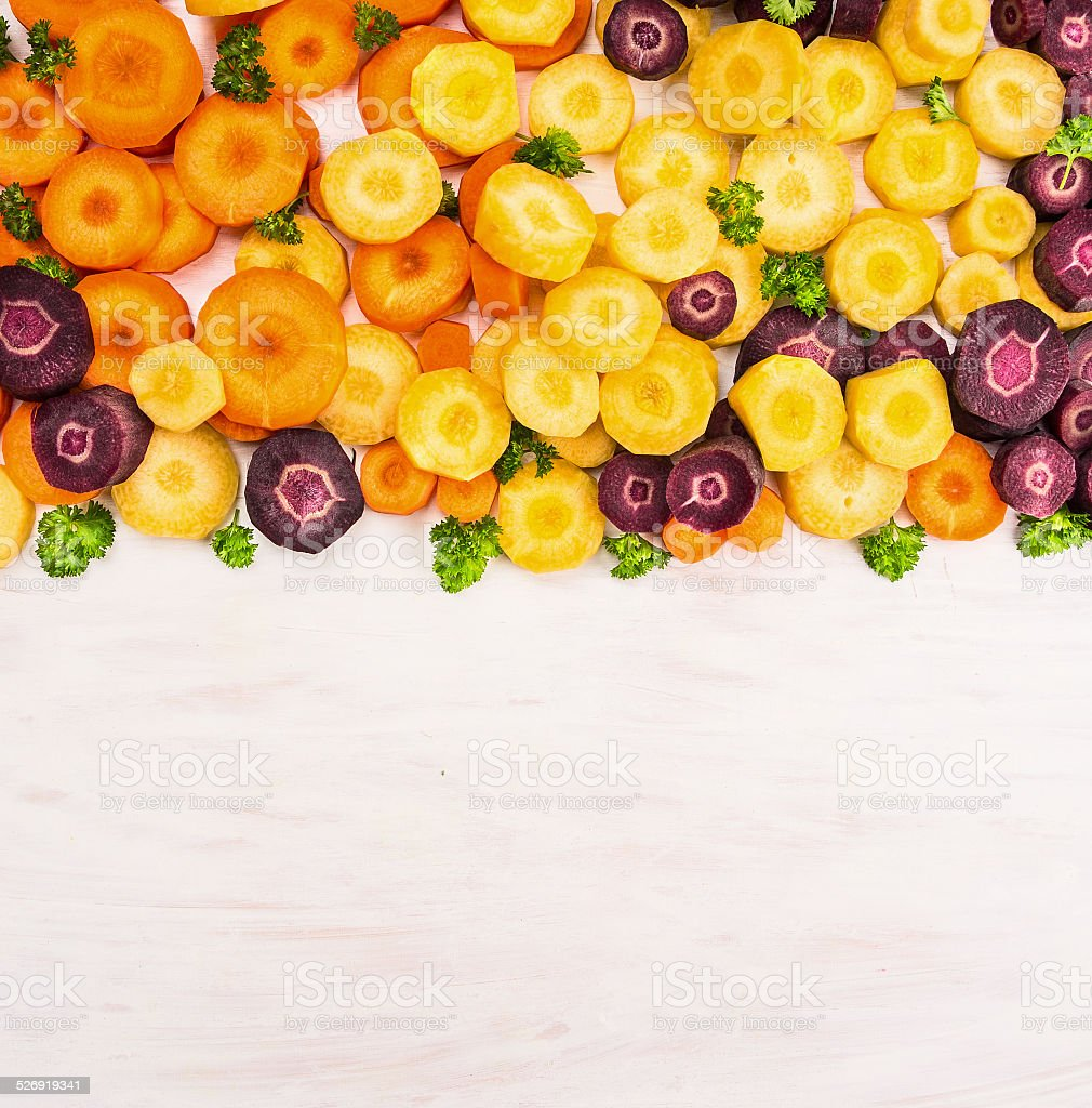 multicolored cutting carrots on white wooden, food background, top view stock photo