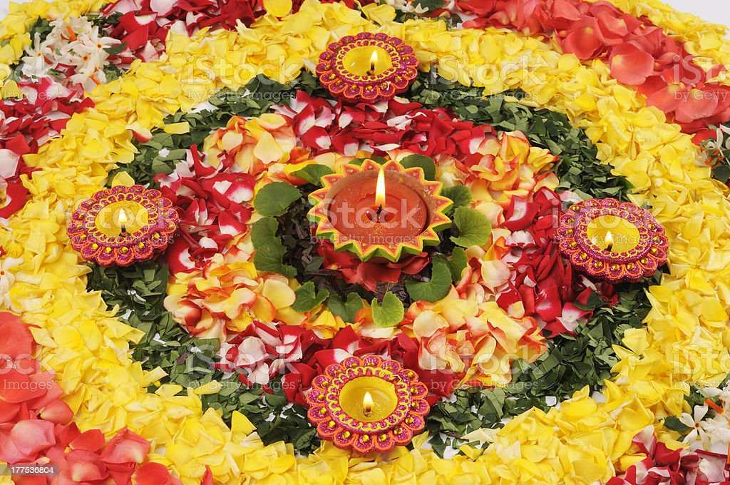 A multicolored Diwali oil lamp surrounded by flower petals stock photo