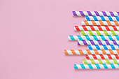 Colorful striped drinking straws on pastel pink background minimal creative concept. Space for copy.