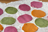 multicolored dyed pieces of raw dough for dumplings