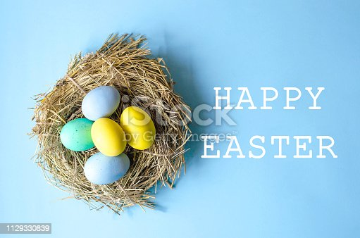 istock Multi-colored Easter eggs in a nest of dry grass. 1129330839
