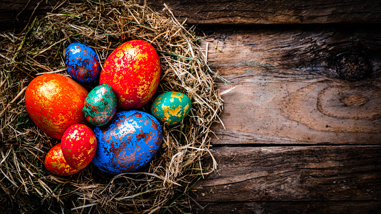 Holidays: Hand painted multi colored Easter eggs in a straw nest shot from above on rustic wooden table. The composition is at the left of an horizontal frame leaving useful copy space for text and/or logo at the right. High resolution 42Mp studio digital capture taken with Sony A7rII and Sony FE 90mm f2.8 macro G OSS lens