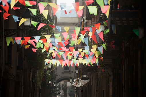 Multicolored feast decorations backlit  in a narrow street.