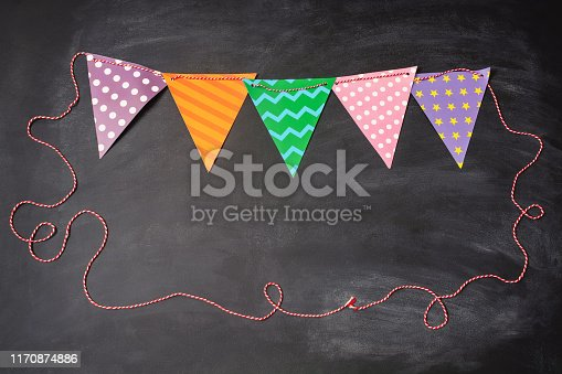 882318110 istock photo Multicolored festive triangular flags on chalkboard with copyspace 1170874886