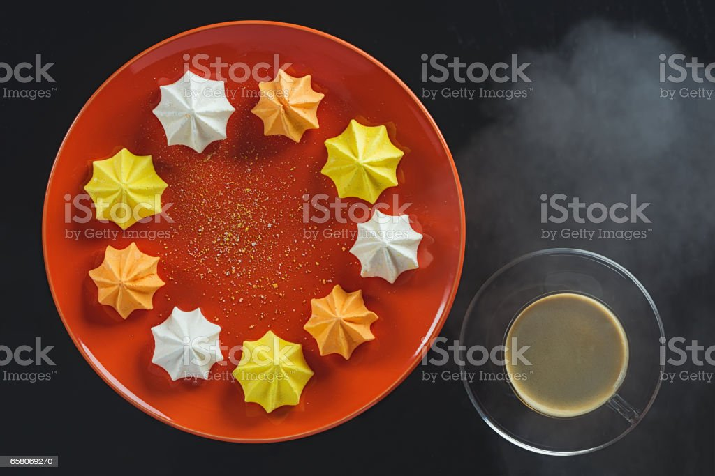 Multi-colored figured cookies on a round orange plate and a cup of hot coffee on a black background стоковое фото