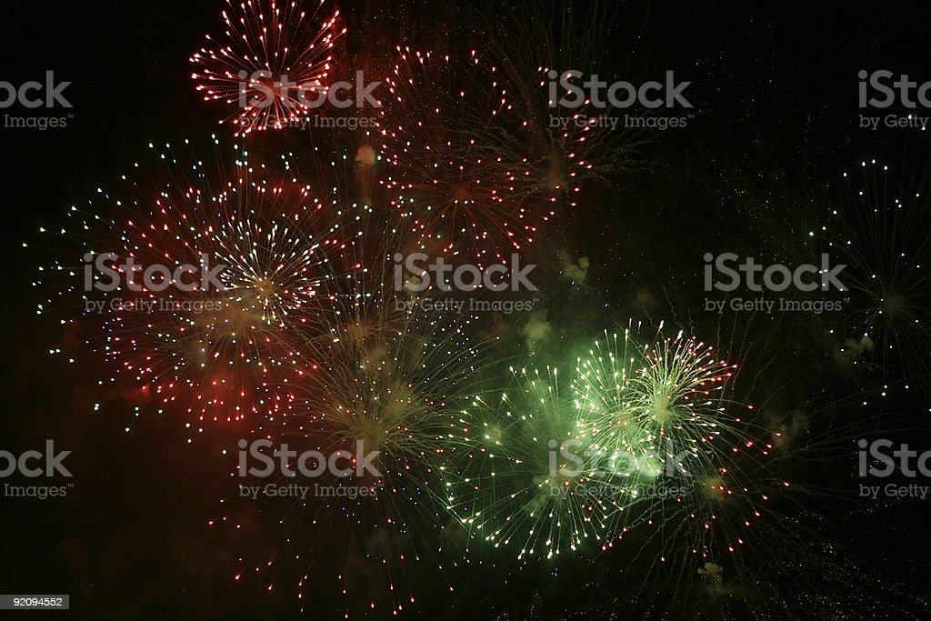 Multicolored fireworks exploding against a dark sky stock photo