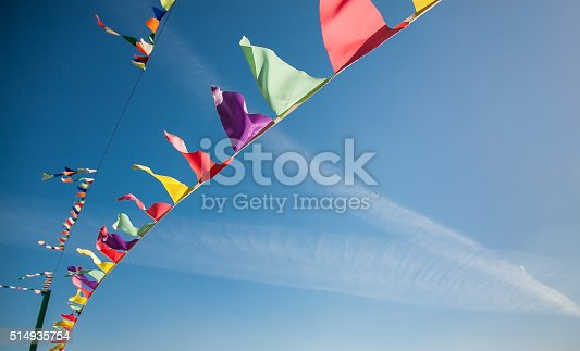 istock Multicolored flags against the blue sky with traces from planes 514935754
