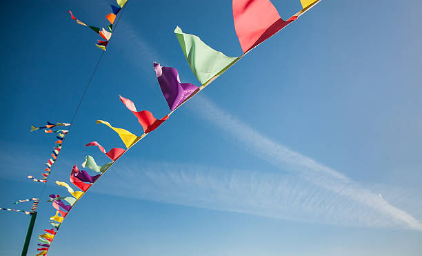 multicolored flags against the blue sky with traces from planes - school fete stock photos and pictures