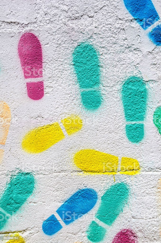 multicolored footprints in a white wall stock photo