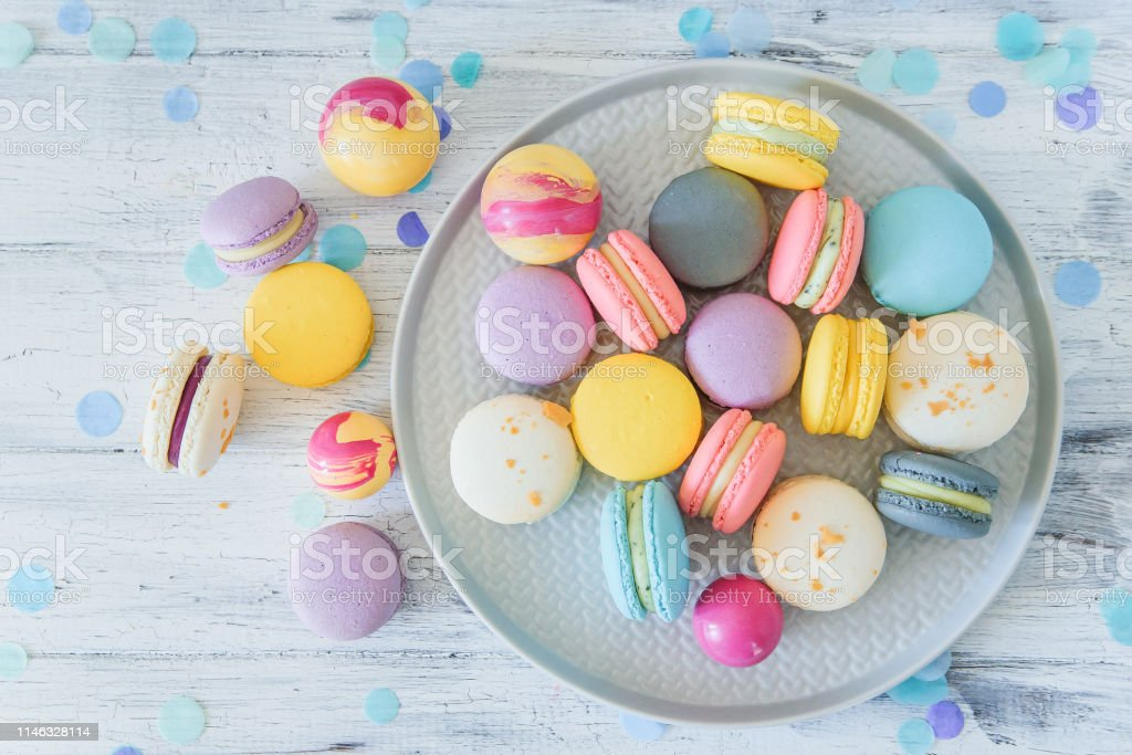 Multicolored French Macaron Cakes On Blue Plate And White Wooden Background White Yellow Pink Purple And Grey French Macarons With Fresh Berries Stock Photo Download Image Now Istock
