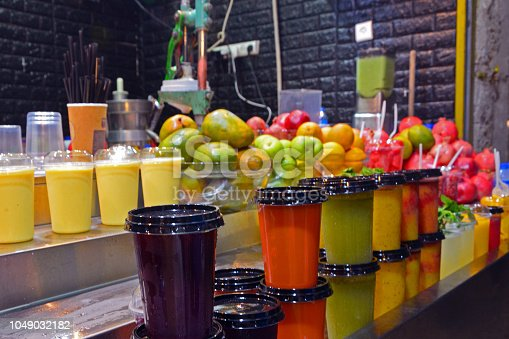 istock Multicolored fruit drinks and juice in plastic cups stand on the counter. market in jerusalem, israel. 1049032182