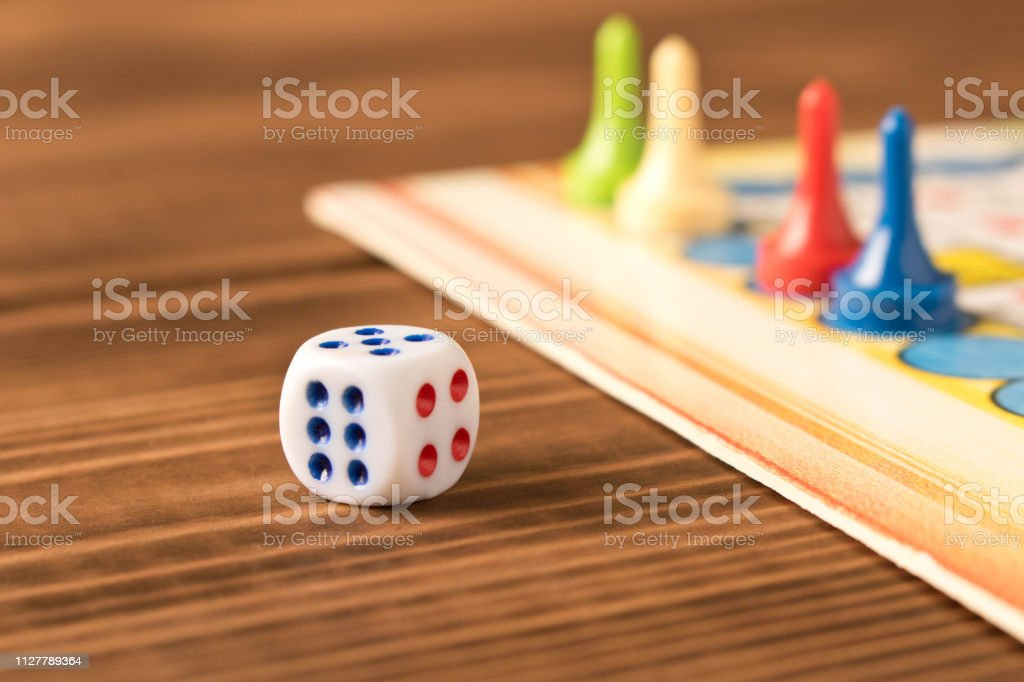 Multicolored Game Chips With Dice On The Playing Board Board