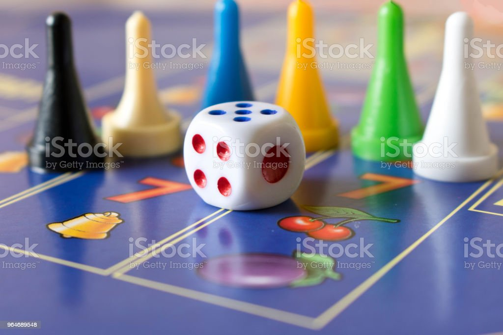 Multi-colored game chips with dice on the playing board. Board game royalty-free stock photo
